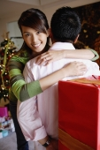Man holding gift behind his back, woman embracing him, smiling at camera - Alex Microstock02