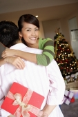 Man holding gift behind his back, woman embracing him - Alex Microstock02
