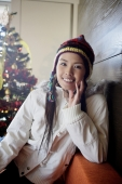 Woman in jacket and cap, smiling at camera, Christmas tree behind her - Alex Microstock02