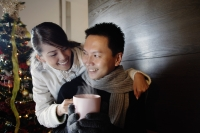 Couple at home, dressed in winter wear, woman passing mug to man - Alex Microstock02