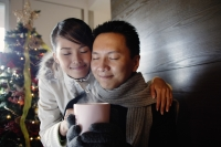 Couple at home, dressed in winter wear, holding mug - Alex Microstock02
