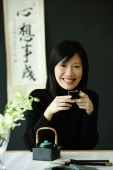 Young woman drinking Chinese tea, smiling at camera - Wang Leng