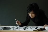 Woman painting Chinese calligraphy - Wang Leng