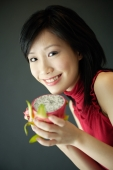 Woman holding cut dragon fruit, smiling at camera - Alex Microstock02