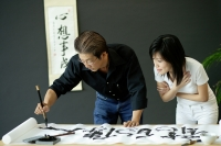 Mature man painting Chinese calligraphy, woman next to him watching - Alex Microstock02