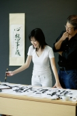 Woman painting Chinese calligraphy, man next to him watching - Alex Microstock02
