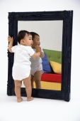 Baby boy standing against mirror - blueduck