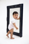 Baby boy standing next to mirror, smiling at camera - blueduck