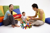 Family with one child, sitting on floor, playing with toys - blueduck