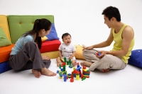 Family with one child, playing with toys, sitting on living room floor - blueduck