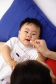 Baby boy lying on back, mother touching his lips - blueduck