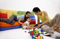 Family with one child, sitting in living room, playing with wooden toy blocks - blueduck