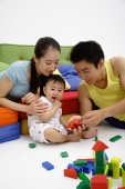 Father, mother and son sitting in living room, playing with wooden toy blocks - blueduck