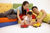 Father, mother and son sitting in living room, playing with toy cars - blueduck