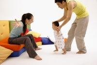 Mother sitting on sofa, arms outstretched, father helping toddler walk towards her - blueduck