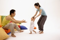 Father sitting on sofa, arms outstretched, mother helping toddler walk towards him - blueduck