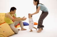 Father sitting on sofa, arms outstretched, toddler walking towards him, guided by the mother - blueduck