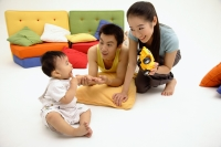 Young parents with one child, bonding in living room - blueduck