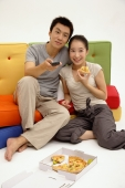 Couple sitting on sofa, woman eating pizza, man holding TV remote control - blueduck