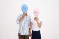Couple standing side by side, holding hands, with balloons over their faces - blueduck