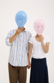 Couple holding hands, with balloons over their faces - blueduck