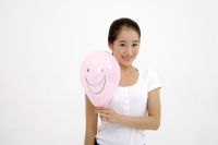 Woman holding pink balloon with smiley face drawn on it - blueduck
