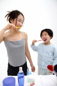 Mother and young daughter brushing teeth, looking at each other - blueduck