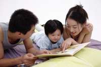 Family with one child lying on bed, reading book - blueduck