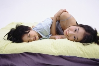 Mother and daughter lying on bed, looking at camera - blueduck