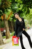 Woman dressed in black, holding shopping bags, smiling - Alex Microstock02