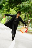 Woman dressed in black, holding shopping bags, walking on road - Alex Microstock02