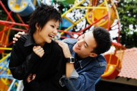 Couple at playground, looking at each other, laughing - Alex Microstock02