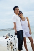 Couple standing on beach with Dalmatian - Alex Microstock02