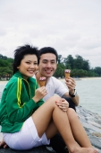 Couple sitting on breakwater, eating ice cream - Alex Microstock02