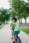 Couple cycling on tandem bicycle, woman looking over shoulder - Alex Microstock02