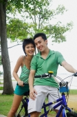 Couple on tandem bicycle, looking at camera - Alex Microstock02