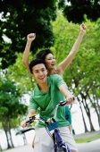 Couple on tandem bicycle, woman raising arms in the air - Alex Microstock02