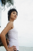 Woman in sleeveless top, standing by sea, hand on hip - Alex Microstock02