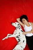 Woman lying on red blanket with Dalmatian - Alex Microstock02