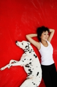 Woman with hands behind head lying down with Dalmatian on red blanket - Alex Microstock02