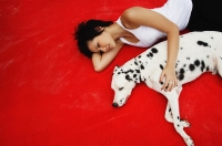 Woman lying down with Dalmatian on red blanket - Alex Microstock02