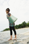 Woman standing on beach, carrying beach bag - Alex Microstock02