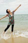 Woman standing in sea, looking up, arms outstretched - Alex Microstock02