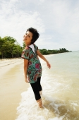 Woman walking on beach, looking over shoulder - Alex Microstock02