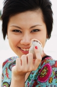 Woman holding shell, smiling at camera, portrait - Alex Microstock02