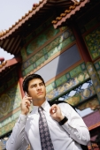 Businessman standing in front of temple gate, holding jacket over shoulder, using mobile phone - Alex Microstock02