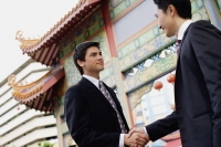 Two businessmen shaking hands, temple gate in the background - Alex Mares-Manton