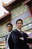 Two businessmen standing, looking at camera, temple gate in the background - Alex Mares-Manton