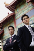 Two businessmen standing side by side, temple gate in the background - Alex Mares-Manton