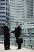 Two businessmen shaking hands, looking at camera, river and buildings in the background - Alex Mares-Manton